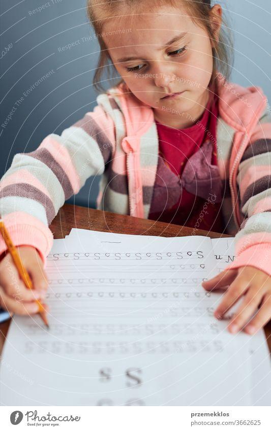 Kleines Mädchen im Vorschulalter lernt widerwillig, Briefe zu schreiben. Kind, das Briefe schreibt und widerwillig eine Schularbeit erledigt. Konzept der Früherziehung