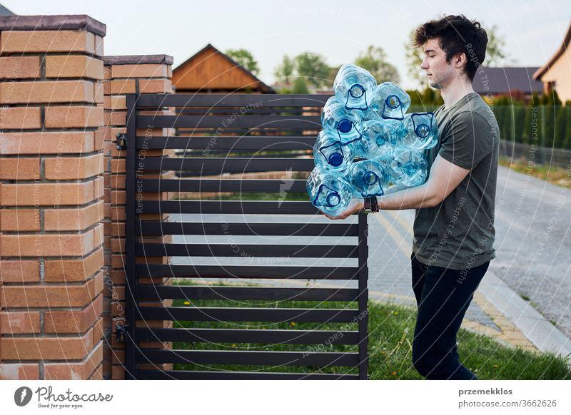 Junger Mann wirft leere gebrauchte Plastikwasserflaschen in den Mülleimer. Sammelt Plastikabfälle zur Wiederverwertung ein. Konzept der Kunststoffverschmutzung und zu vieler Kunststoffabfälle. Umweltproblematik