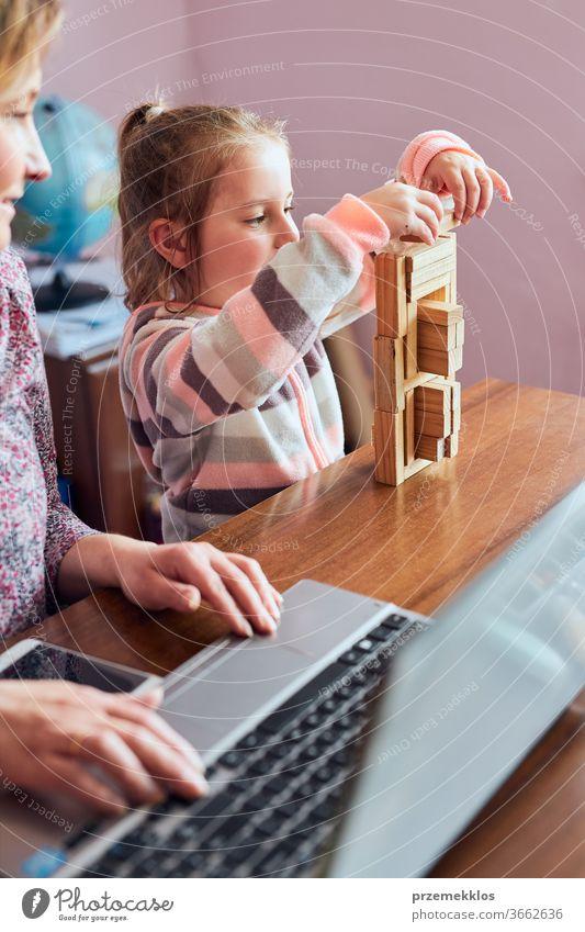Eine Mutter, die während eines Video-Chat-Call-Stream-Online-Kurses von zu Hause aus auf einem Laptop arbeitet, während ihre Tochter mit einem Ziegelsteinspielzeug spielt. Frau sitzt am Schreibtisch vor dem Computer und schaut auf den Bildschirm