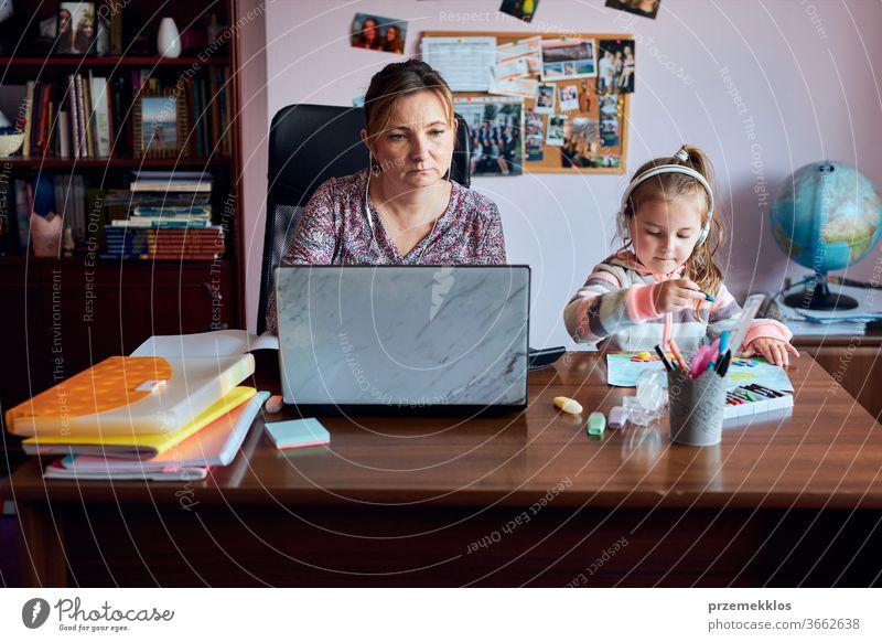 Eine Mutter, die während eines Video-Chat-Call-Stream-Online-Kurses auf einem Laptop von zu Hause aus aus der Ferne arbeitet, während ihre Tochter Zeichnungen anfertigt, herumspielt und sich Geschichten anhört. Frau sitzt am Schreibtisch vor dem Computer und schaut auf den Bildschirm
