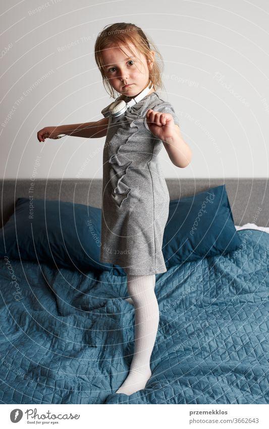 Kleines Mädchen singt mit Kopfhörerkabel in der Hand und imitiert sich selbst als echte Sängerin. Kind, das Spaß daran hat, beim Tanzen zu springen und Musik auf dem Bett im Schlafzimmer zu Hause zu hören