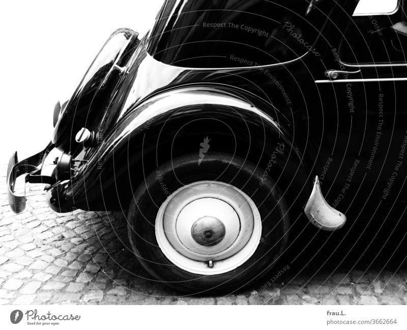 Gepflegt mit glänzendem Lack ließ sich der Oldtimer sein prächtiges Hinterteil von der Sonne wärmen. Autotür Straßenrand Kopfsteinpflaster alt PKW Fahrzeug