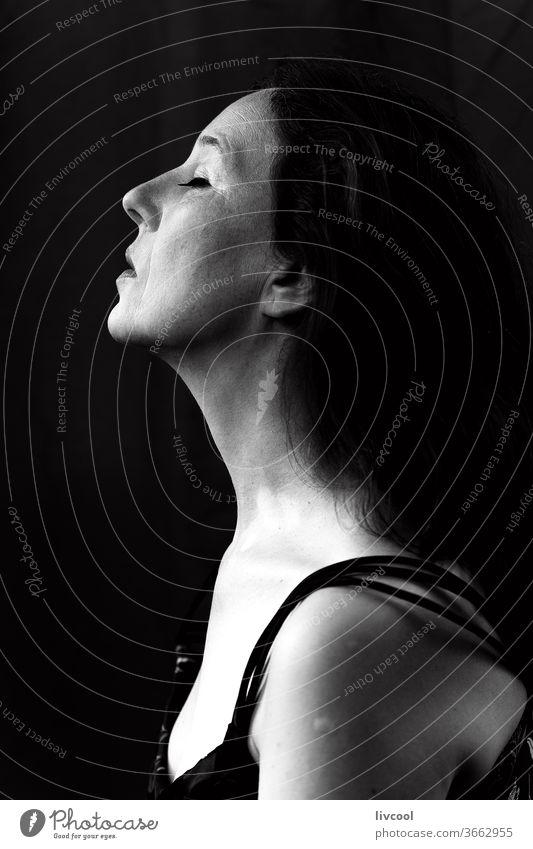 schwarz-weißes Frauenprofil-Portrait Porträt schön schwarz auf weiß Profil traurige Haltung dunkel schwarzer Hintergrund Menschen romantisch romantische Haltung