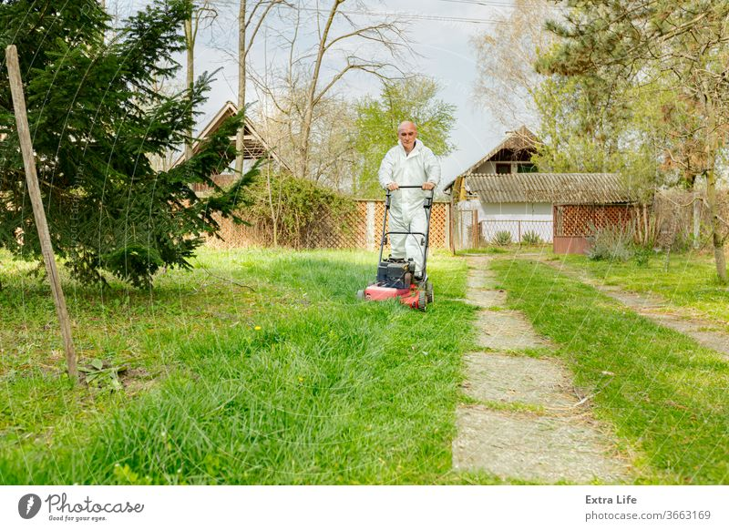 Landwirt in Schutzkleidung mäht Rasen in einem Garten mit einem Benzinrasenmäher Hinterhof Blütezeit botanisch Pflege Schermaschine kultivieren geschnitten