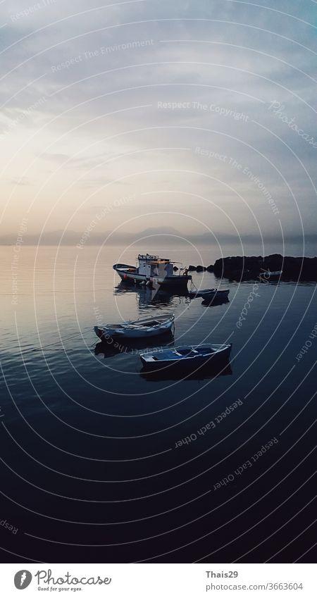 früher Sonnenaufgang ruhiges Meer, keine Wellen, Sonnenlicht spiegelt sich auf dem Wasser, kleine Fischerboote ruhen sich aus, schöner Horizont Meereslandschaft, Italien, Napoli, Neapel