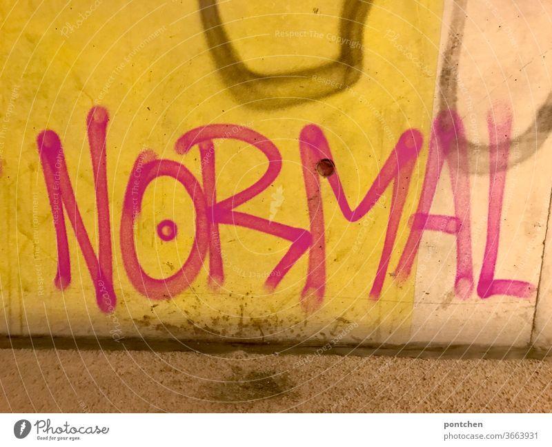 Das Wort normal als Graffiti auf einer  Mauer  in  einer unterführung Normal wort graffiti Schriftzeichen Wand Buchstaben Text Schmiererei Alltag Tag