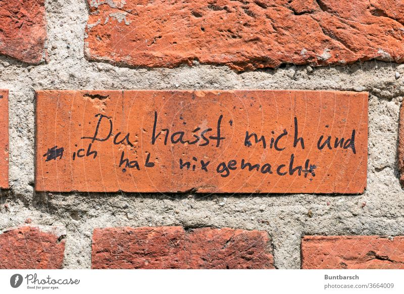 """Schriftzug auf Ziegelwand: """"Du hasst mich und ich hab nix gemacht"""" Hass Text Wand Außenaufnahme Buchstaben Schriftzeichen Wort Menschenleer Mauer Kommunikation"""