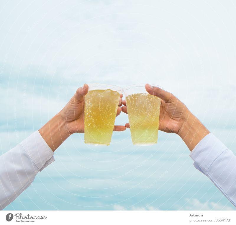 Party feiern, Hände halten Getränkebiere mit Plastikgläsern und jubeln über den Erfolg mit einem schönen Himmel als Hintergrund Erwachsener Alkohol alkoholisch