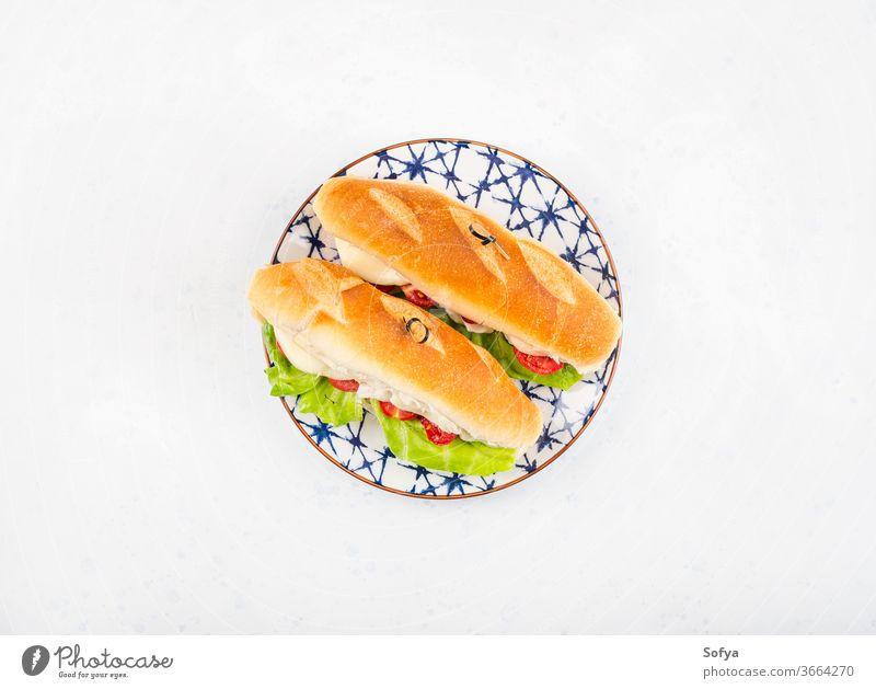 Baguette-Sandwich mit Tomaten und Käse Belegtes Brot U-Boot Mittagessen Sub hoagie flache Verlegung geschmolzen Gemüse Draufsicht Salatbeilage hölzern