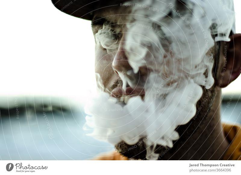 Ein junger, bärtiger Mann bläst dicken Rauch aus seinem Mund aus einem Vape. Raps Rauchen Cloud Jugend Erwachsener Teenager Zigarette Rauchwolke rauchend Sucht