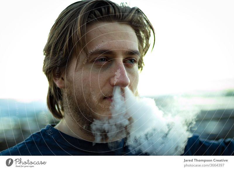 Ein junger Mann schnäuzt sich Rauch aus der Nase. Raps Jugendkultur Zigarette Rauchen Erwachsene Jugendliche Zigarettenrauch Rauch-Trick