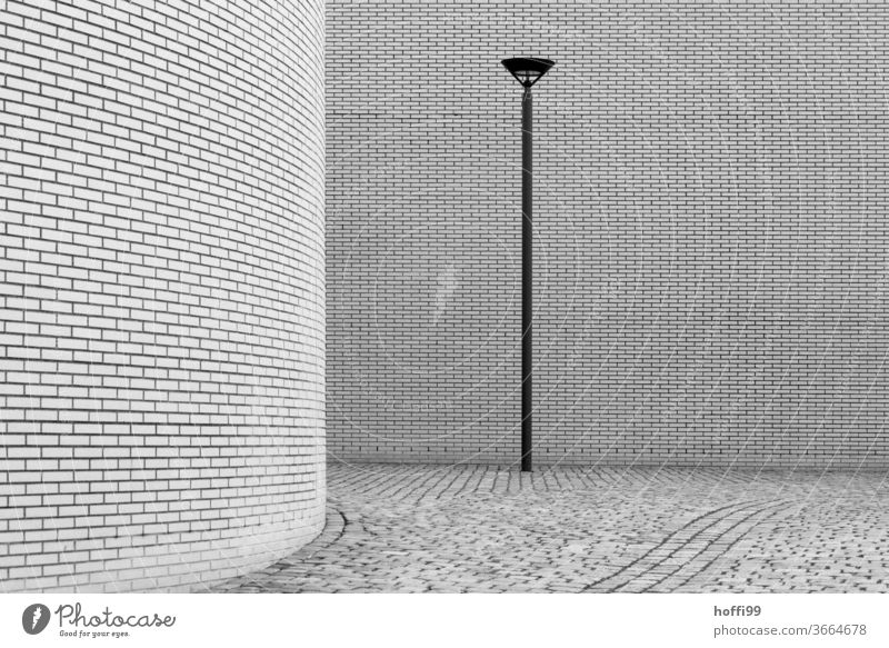die Lampe bringt Erleuchtung - die Rundung verbirgt, aber das Ganze ist eine Wohltat für den Betrachter minimalistischer Szenen Laterne Laternenpfahl Wand Mauer