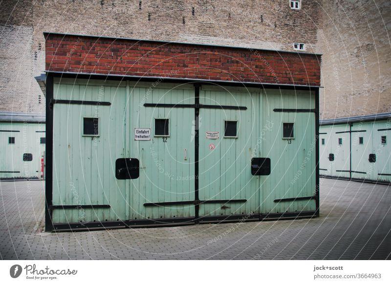 freundliche Mehrzweckgaragen aus DDR-Zeiten Garage Architektur türkis Prenzlauer Berg Brandmauer Garagentor retro Zahn der Zeit Smiley Illusion Lächeln