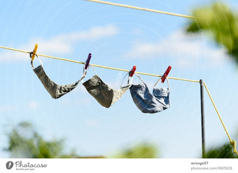 Frisch gewaschen hängen 3 selbstgenähte Mundschutzmasken zum Trocknen auf der Wäscheleine 3 Stück frisch gewaschen selbstgemacht trocknen Sauberkeit Waschtag