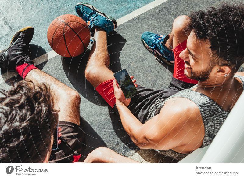junger Mann ruht sich nach dem Basketballspiel aus und benutzt sein Smartphone mit seinem Freund Sport Ball Spiel sportlich soziale Netzwerke wettbewerbsfähig