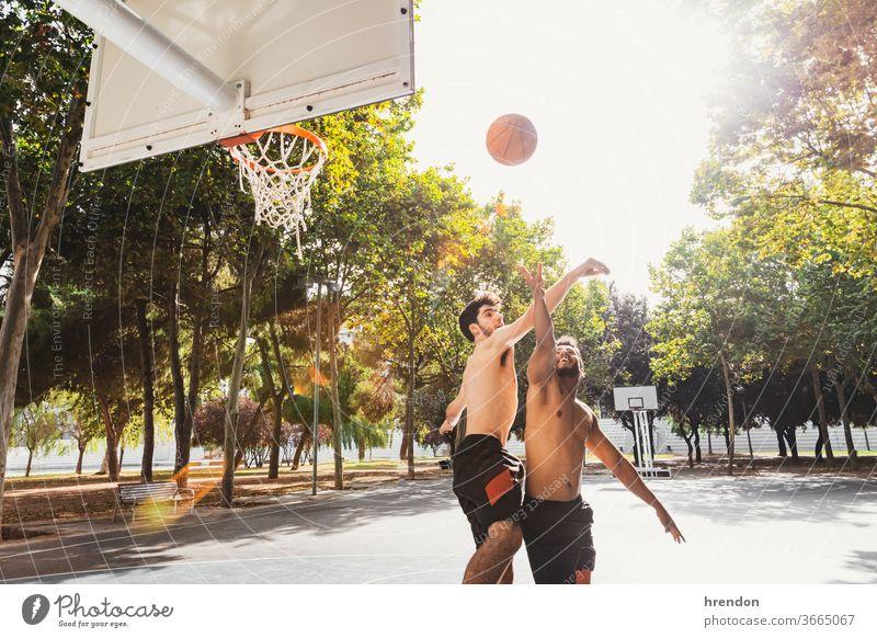 zwei junge Männer spielen Basketball im Freien Sport Konkurrenz Ball Spiel sportlich wettbewerbsfähig Spielen Übung männlich trainiert. anstrengen Hobby