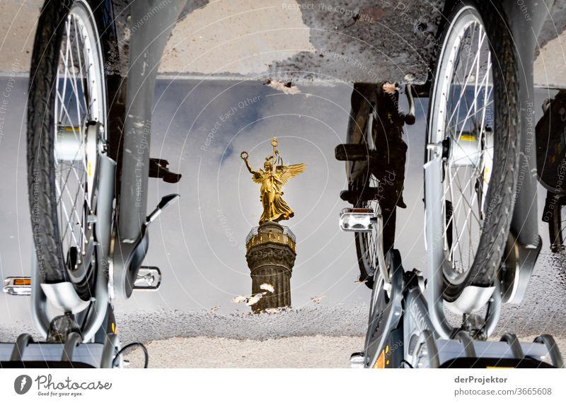 Siegessäule in einer Pfützenspiegelung mit Fahrrädern Stadtzentrum Menschenleer Sehenswürdigkeit Wahrzeichen Denkmal Gold Statue Farbfoto Außenaufnahme