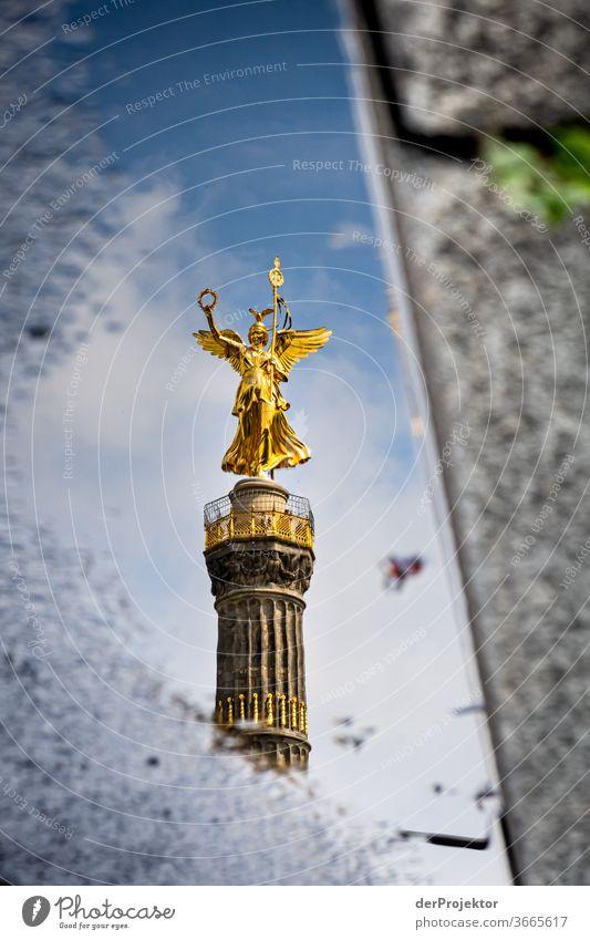 Siegessäule in einer Pfützenspiegelung mit Asphalt und Bordsteinkante Stadtzentrum Menschenleer Sehenswürdigkeit Wahrzeichen Denkmal Gold Statue Farbfoto