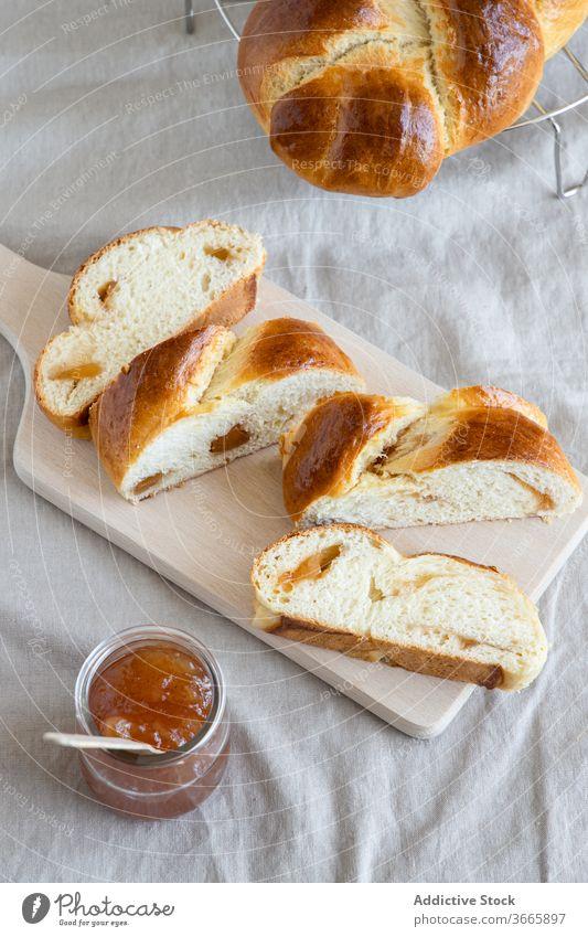 Brioche auf Holzbrettchen bei Marmelade im Glas Brötchen lecker selbstgemacht Gastronomie Scheibe Gebäck süß Glasgefäß gebacken Ware Schneidebrett Küche