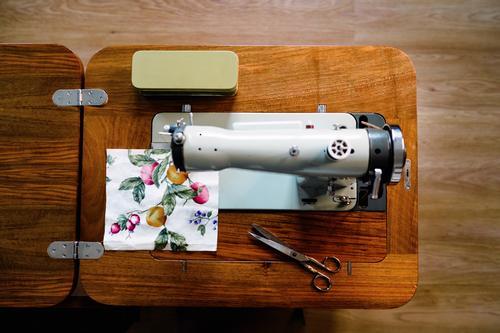 Nähmaschine und Stoffmuster mit Fruchtmuster in der Werkstatt Gewebe Probe Schere Handwerk Gerät Muster Kleinunternehmen Atelier stechend Instrument