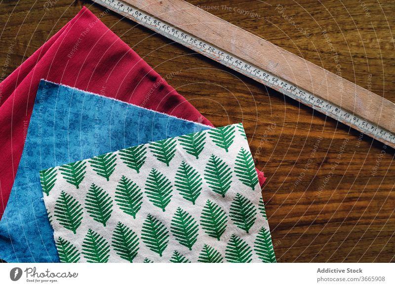 Satz sortierter Stoffmuster mit bunten Mustern im Atelier Textil Probe Lineal Basteln Ornament Baumwolle Kleinunternehmen hölzern Tisch farbenfroh Gewebe
