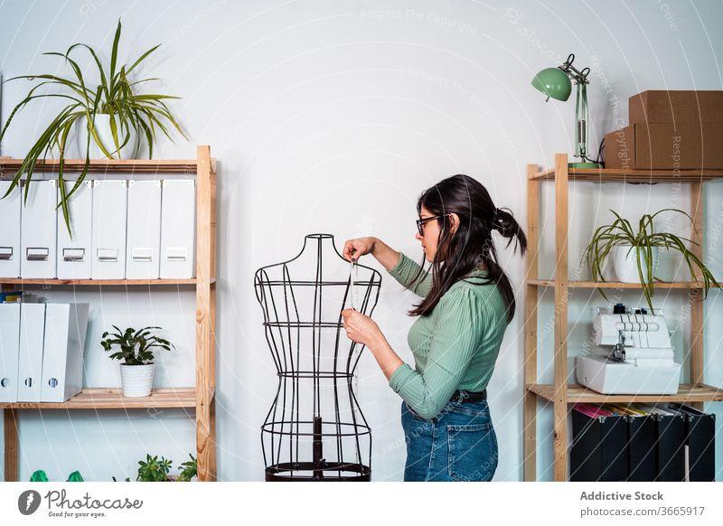 Frau nimmt Messungen in einer verkabelten Attrappe vor Mode Bekleidung Dummy messen Draht altehrwürdig retro Metall Figur Antiquität Nähen weiß