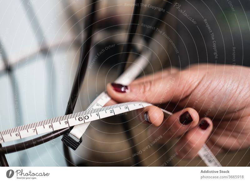 Anonyme Frau, die Messungen an einem verkabelten Dummy vornimmt Mode Bekleidung Meter messen Draht Metall Figur Nähen Schaufensterpuppe Formular Designer