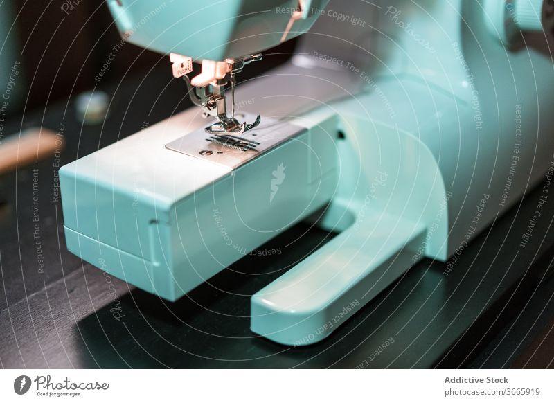 Moderne Metallnähmaschine im Atelier Nähmaschine Handwerk Gerät Kleinunternehmen stechend Instrument professionell Textil hölzern Tisch Form farbenfroh Material