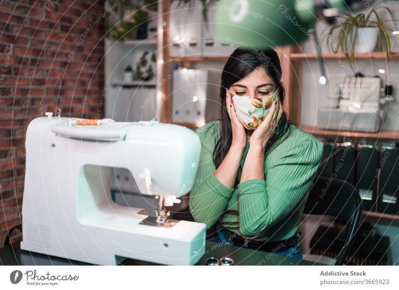 Schneidernähen auf einer Maschine in der Nähe einer Ziegelwand im Atelier Nähmaschine Basteln Probe Muster Lampe Kleinunternehmen Backsteinwand Werkstatt Gewebe