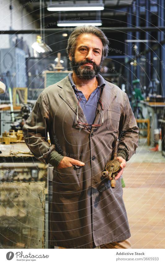Ernster ethnischer Handwerker mit goldenem Gegenstand in der Werkstatt stehend Juwelier Basteln Objekt ernst Hand-in-Tasche Uniform Kleinunternehmen Atelier