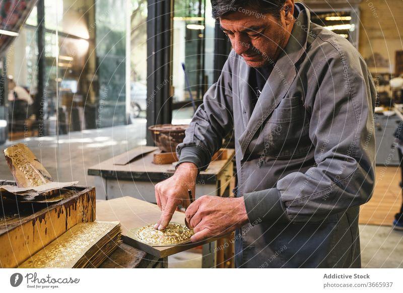 Reifer Juwelier, der im Workshop mit einem Bleistift Goldgegenstände herstellt Arbeit gold Metall Werkzeug Prozess Basteln konzentriert Kleinunternehmen