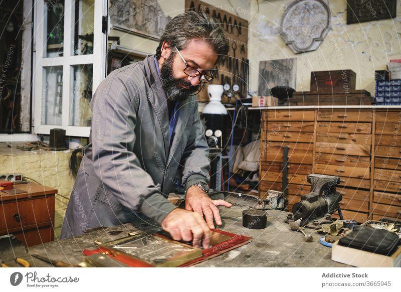 Handwerker reinigt Goldgravur im Atelier Kunsthandwerker Sauberkeit Gravur Gewebe golden Rahmen Kunstgewerbler Kleinunternehmen Werkstatt Prozess Goldschmied