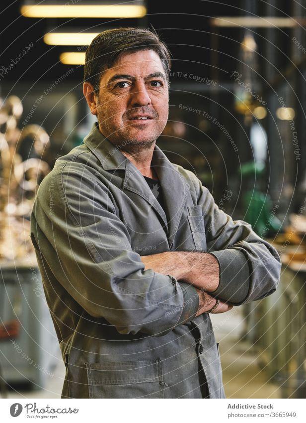 Porträt eines in der Werkstatt stehenden Handwerkers Kunsthandwerker Basteln Glück Uniform Kleinunternehmen Atelier gold Goldschmied Arbeitsbereich solide