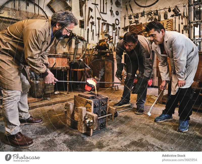 Gruppe von Handwerkern, die eine Form mit Metall füllen Metallarbeiten gießen Schimmelpilze heiß zerlaufen eingießen besetzen Goldschmied Prozess Arbeit Männer