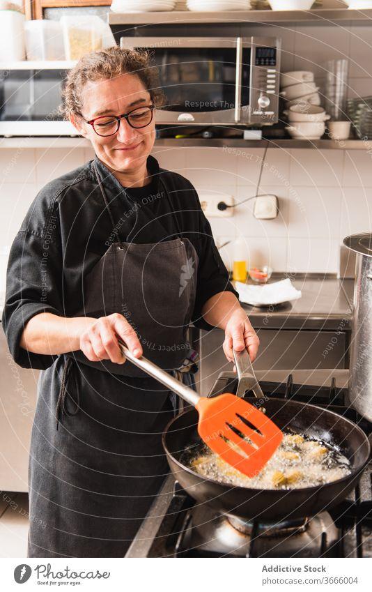 Braten von Artischocken in der Küche eines Restaurants Lebensmittel Feinschmecker Küchenchef Speise Essen zubereiten Mahlzeit frisch geschmackvoll Abendessen