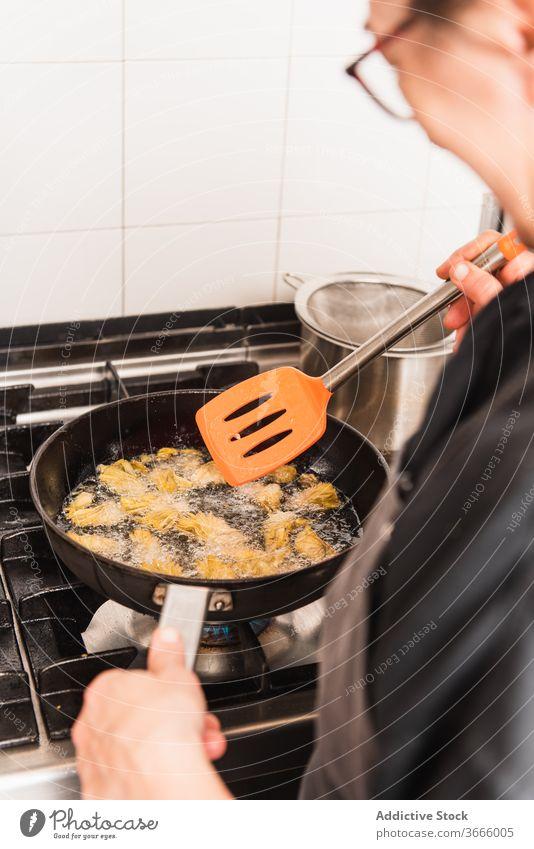 Anonymer Chefkoch brät Artischocken in der Küche. Lebensmittel Feinschmecker Küchenchef Speise Essen zubereiten Mahlzeit frisch Restaurant geschmackvoll