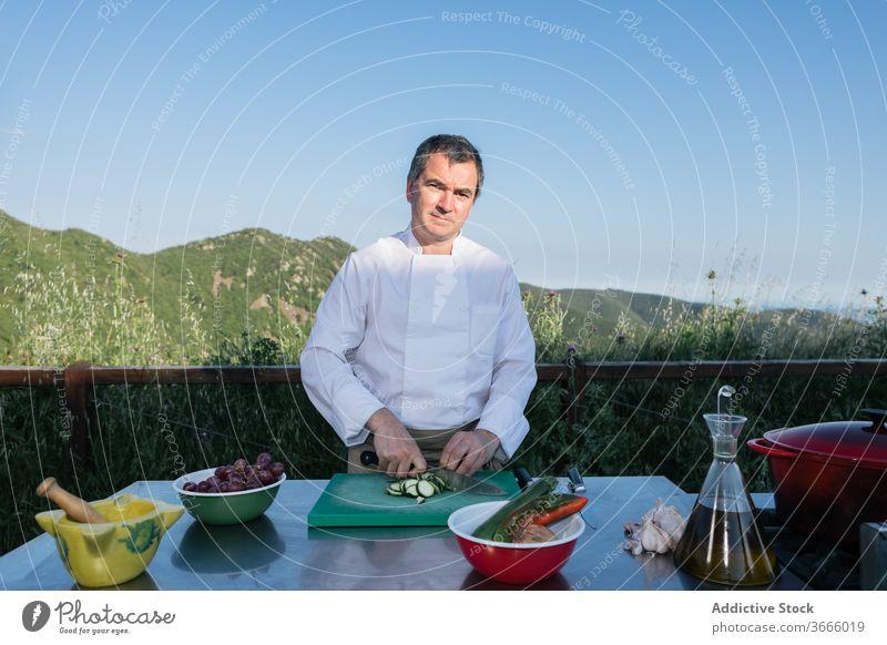 Männlicher Koch schneidet Gemüse für die Zubereitung des Abendessens in der Außenküche Mann geschnitten Salatgurke Küchenchef vorbereiten Speise frisch
