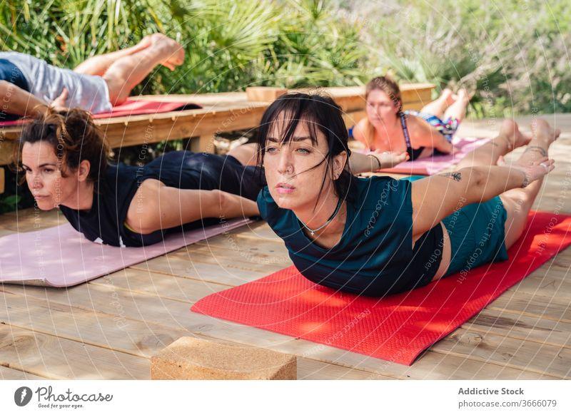 Personen, die während des Yoga-Trainings Körperhaltung einnehmen Frauen Menschen salabhasana Heuschrecke Lager Lektion Wellness Dehnung Ausbilderin Asana