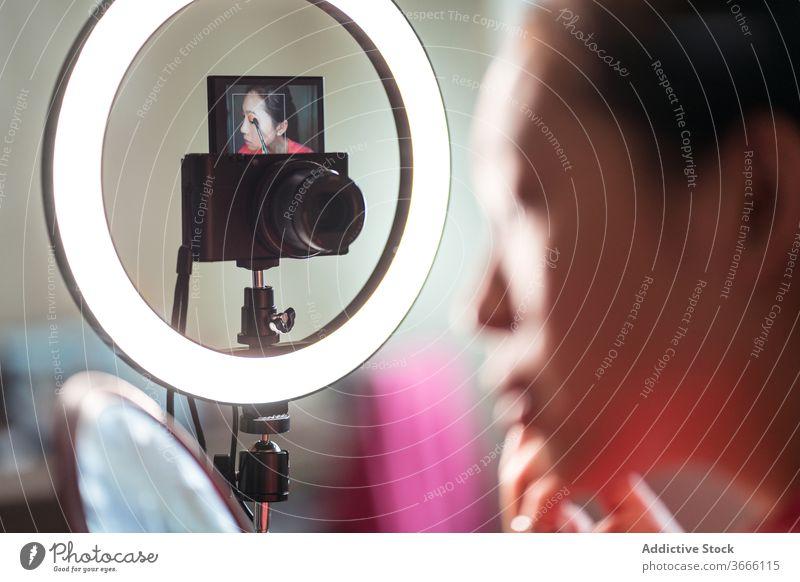 Schönheitsbloggerin zeigt Pinsel für Make-up vlog Blogger Frau Bürste Kosmetik Aufzeichnen Video manifestieren positiv jung asiatisch ethnisch zeigen Lächeln
