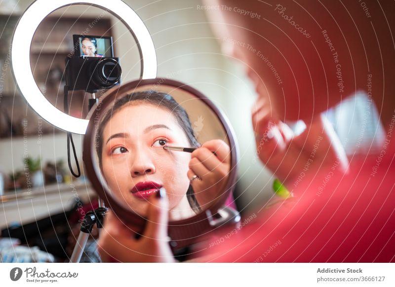 Asiatische Schönheitsbloggerin beim Schminken vlog Blogger Frau bewerben Make-up Lidschatten Kosmetik Video schießen Influencer Bürste Auge Spiegel Aufzeichnen