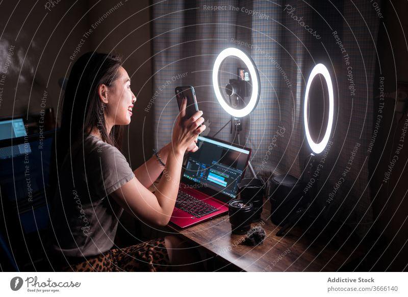 Fröhlicher Blogger demonstriert Smartphone während Videoaufnahmen zeigen Frau manifestieren Fotokamera soziale Netzwerke teilen schießen Influencer Funktelefon