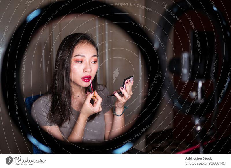 Schönheitsbloggerin, die sich während des Shootings schminkt vlog Blogger Frau Make-up bewerben Kosmetik Fundament Aufzeichnen Video jung asiatisch ethnisch