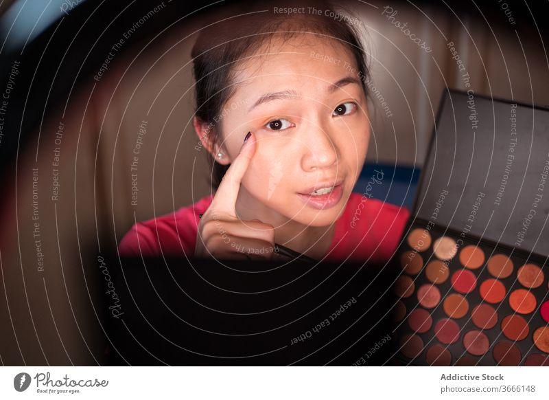 Schönheitsbloggerin mit Make-up-Palette nimmt Video auf vlog Blogger Frau Kosmetik Aufzeichnen manifestieren positiv jung asiatisch ethnisch zeigen Lächeln