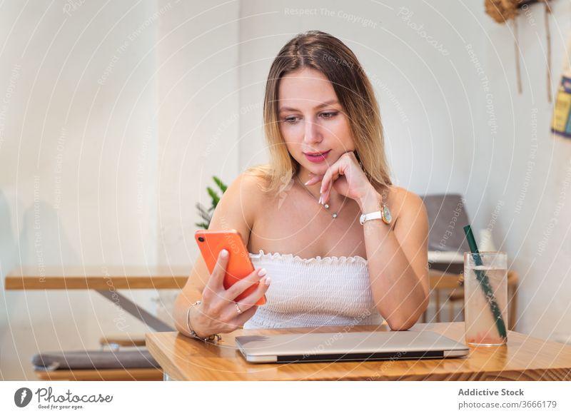 Positive junge Frau benutzt Smartphone, während sie mit Laptop und Saft am Tisch sitzt lesen Nachricht Pause Café Haare berühren besinnlich Gerät Apparatur