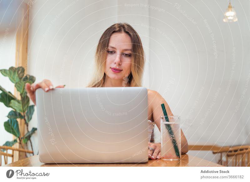 Junge Geschäftsfrau benutzt Laptop während Fernarbeit im Café Frau Arbeit freiberuflich abgelegen Tippen beschäftigt frisch Limonade Browsen Internet jung