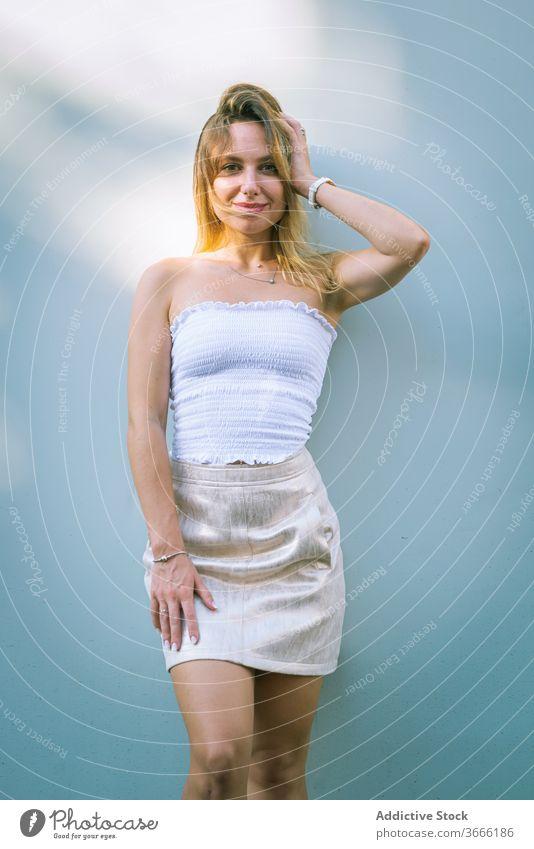 Positive junge Blondine, die an einem sonnigen Tag an einer weißen Wand steht Frau selbstbewusst Lächeln Sonnenlicht Schatten Stil Porträt Tastkopf tagsüber