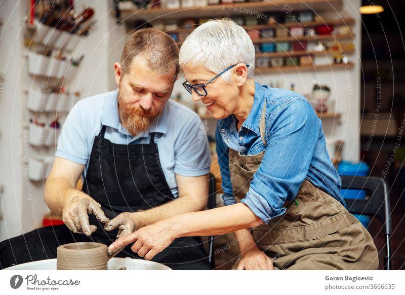 Ältere Frau dreht Ton auf einer Drehscheibe mit einem Lehrer im Töpferkurs Dame spinnen Belehrung Ausbilderin lernen Form Finger Topf drehen. Keramik gekonnt