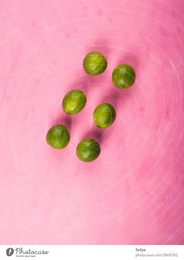 Frische, ganz grüne Limetten auf rosa Hintergrund Kalk flache Verlegung Urlaub Zitrusfrüchte Barista farbenfroh Bestandteil Frucht Cocktail trinken Party rot