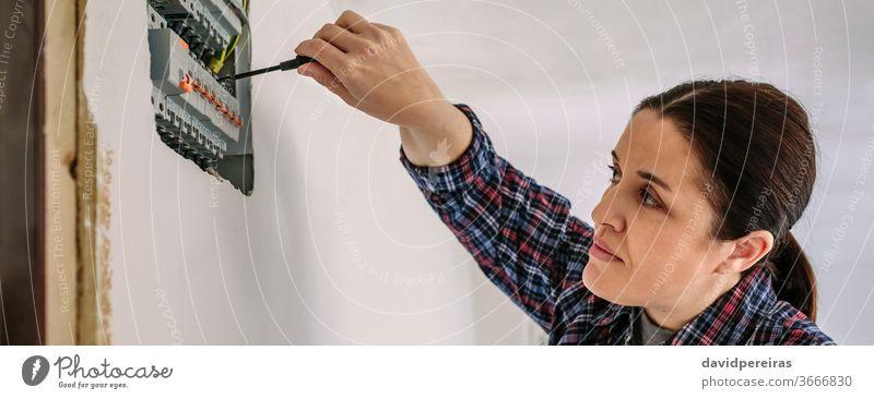 Elektriker, der an der Verteilertafel eines Hauses arbeitet Frau Elektrotechniker Schraubendreher Elektromonteur Elektroinstallation Besichtigung Prüfung