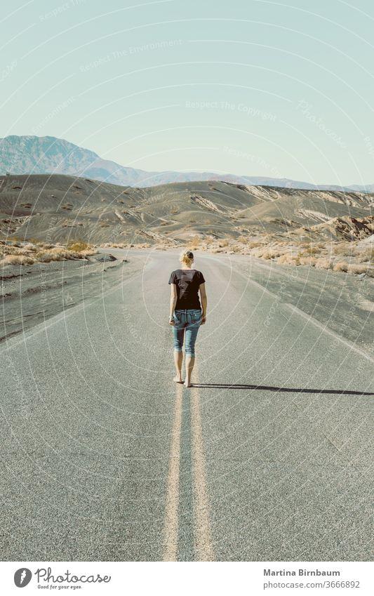 Eine Frau geht barfuss auf einer leeren Strasse im Death Valley laufen eine Person Kaukasierin Tal des Todes der Weg nach vorn Fluchtpunkt Freiheit Landschaft